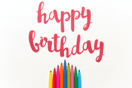 Inspirational phrase Happy birthday for greeting cards and posters drawing with red marker on white paper. Top view of lettering, bunch of colourful markers