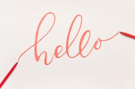 Greeting phrase Hello handwritten with orange marker on white paper