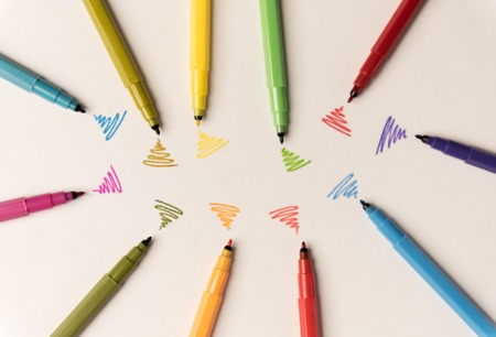 Wi-fi lines drawn with different colorful markers on white paper. Markers lying in group
