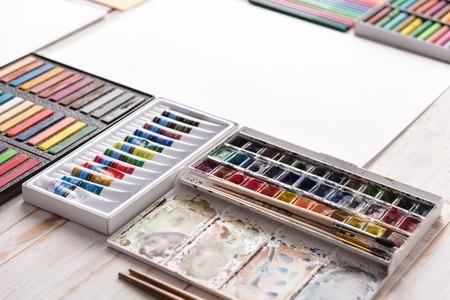 Kleurrijke pastelkleur en dozen met verschillende acrylverf op houten witte lijst aangaande werkplaats van kunstenaar Stockfoto