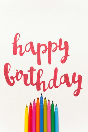 Colourful phrase Happy birthday for greeting cards and posters drawing with red marker on white paper. Top view of lettering, bunch of colourful markers Stock Photo