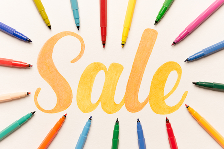 Top view of hand written calligraphy lettering Sale in bunch of colorful markers on white paper
