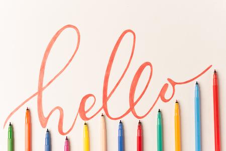 Groet motiverende kleurrijke zin 'Hallo' handgeschreven met oranje markering op wit papier. Bovenaanzicht van belettering in bos van kleurrijke markeringen Stockfoto