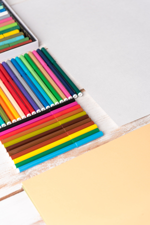 Top view of different colorful markers in boxes on white table