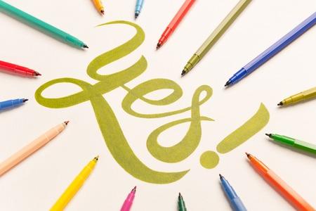 Groene hand tekening zin Ja op wit vel met groene markeringen. Hoogste mening van het van letters voorzien in bos van kleurrijke tellers