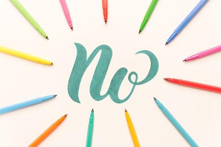 Groene hand getekende zin NO op wit vel tussen kleurrijke markeringen. NEE in kader van markeringen Stockfoto