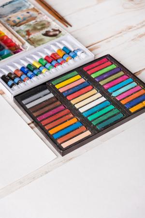Pastel en doos met acrylverf op houten witte lijst op werkplaats van kunstenaar