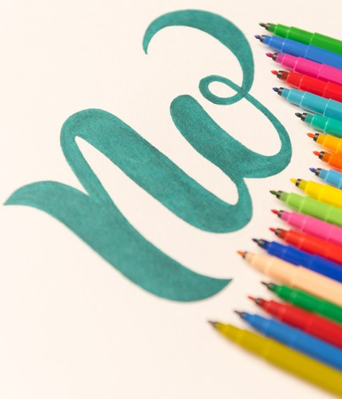 Picture of hand drawn green phrase NO isolated on wave of colorful markers