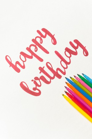 Colourful phrase Happy birthday for greeting cards and posters drawing with red marker on white paper. Top view of lettering, bunch of colourful markers Banco de Imagens