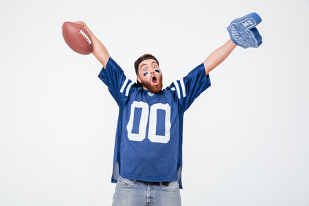 Photo of screaming man fan in blue t-shirt standing isolated over white background. Looking camera holding rugby ball.