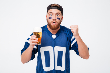 Photo of concentrated man fan in blue t-shirt standing isolated over white background. Looking camera drinking beer. Reklamní fotografie
