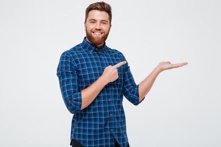 Opgewekte glimlachende gebaarde mens die vinger richt op exemplaarruimte op zijn die palm over witte achtergrond wordt geïsoleerd