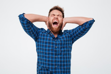 Portrait of an annoyed bearded man covers his ears and screaming while standing isolated over white background