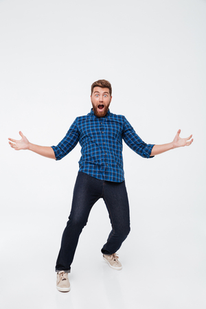 Full length portrait of a happy excited bearded man screaming and gesturing with hands isolated over white background Stock Photo