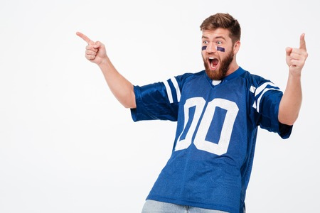 Screaming excited man fan in blue t-shirt standing isolated over white background. Looking aside.