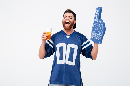Picture of emotional man fan in blue t-shirt wearing fan finger number one glove standing isolated over white background. Looking aside drinking beer.