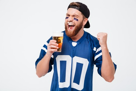 Photo of excited screaming man fan in blue t-shirt standing isolated over white background. Looking aside drinking beer make winner gesture. Reklamní fotografie