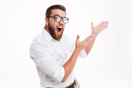 Excited bearded man in eyeglasses pointing away at copy space with two arms isolated over white background Stok Fotoğraf