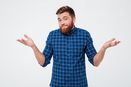 Confused young bearded man standing and shrugging shoulders isolated over white background