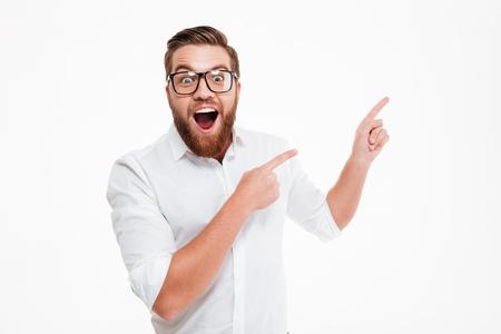 Gelukkige opgewekte gebaarde mens die in oogglazen op exemplaarruimte met twee die vingers richten over witte achtergrond worden geïsoleerd Stockfoto