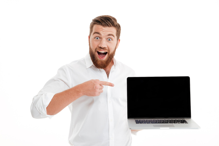 Excited happy bearded man pointing finger at blank screen laptop computer isolated over white background Stock Photo