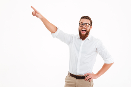 Happy excited bearded man in eyeglasses pointing finger away at copy space isolated over white background