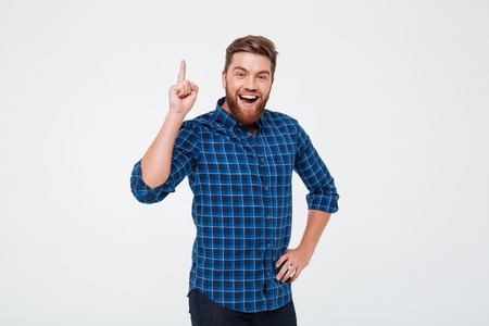 Happy cheerful bearded man pointing finger up and having an idea while standing isolated over white background Stockfoto