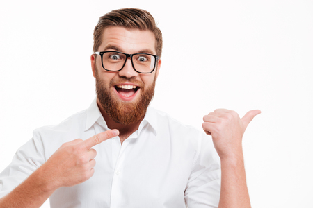 Excited cheerful bearded man in eyeglasses pointing away at copy space with two fingers isolated over white background