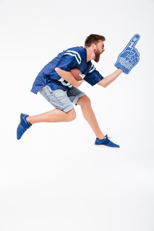Picture of screaming man fan in blue t-shirt jumping isolated over white background. Looking aside holding rugby ball. Reklamní fotografie