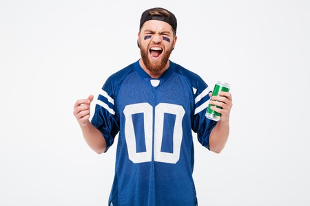 Image of excited man fan in blue t-shirt standing isolated over white background. Looking camera holding beer bottle.
