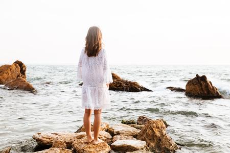 Back view of brunette woman in light summer dress posing on rocks near the sea
