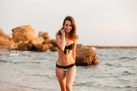 Smiling brunette woman in bikini walking on beach and looking at the camera