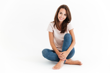 Happy brunette woman sitting on the floor and looking at the camera over white background Stock Photo