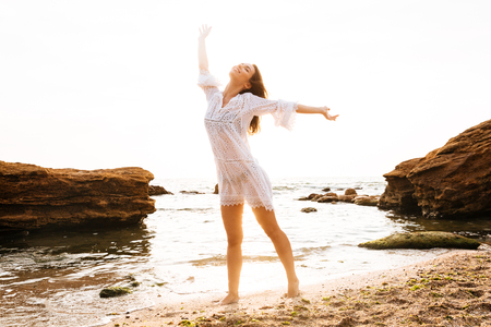 Full length image of happy woman in light summer dress posing with closed eyes on beach 版權商用圖片