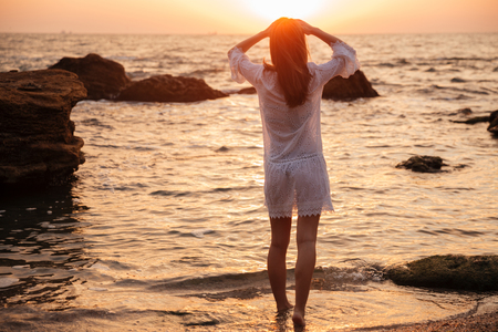 Back view of Brunette woman in light summer dress walking on beach and looking on sunset Stock Photo - 86897621