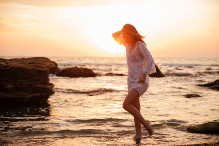 Full length side view image of young brunette woman in light summer dress walking near the sea on sunset Stock Photo