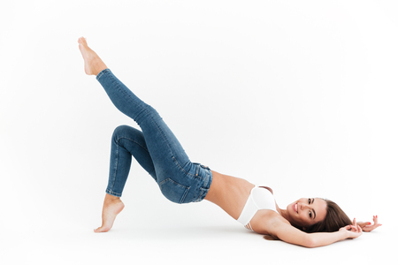 Side view of Smiling woman in bra and jeans lying and posing on the floor and looking at the camera over white background 免版税图像