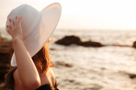 Sluit omhoog zijaanzichtbeeld van donkerbruine vrouw in hoed en bikini die op overzeese lijn kijken