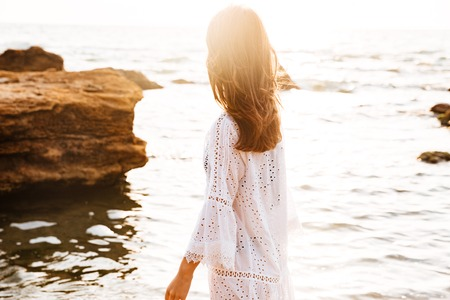 Side view of brunette woman in light summer dress walks on the beach