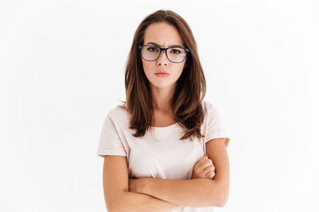 Serious woman in eyeglasses posing with crossed arms and looking at the camera over white background