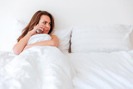 Boze verstoorde vrouw die in leeg bed ligt en iemand thuis roept Stockfoto