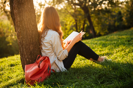 Side view of beauty brunette woman sitting near the tree with book in park and looking away