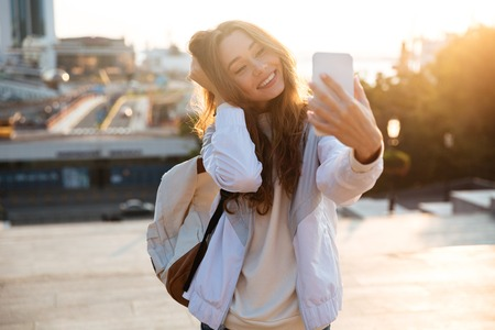 Happy brunette woman in autumn clothes making selfie on smartphone outdoors Reklamní fotografie