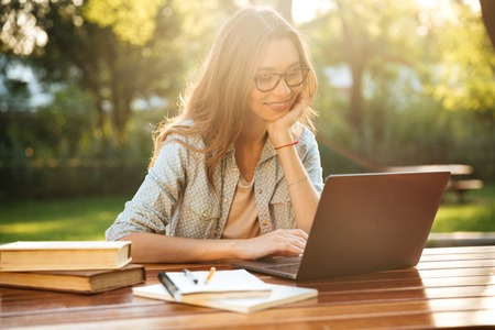 Smiling brunette woman in eyeglasses sitting by the table in park with books and using laptop computer Imagens