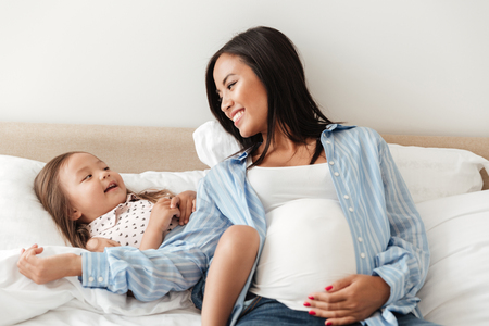Happy smiling pregnant asian woman having fun with her daughter while sitting on bed together