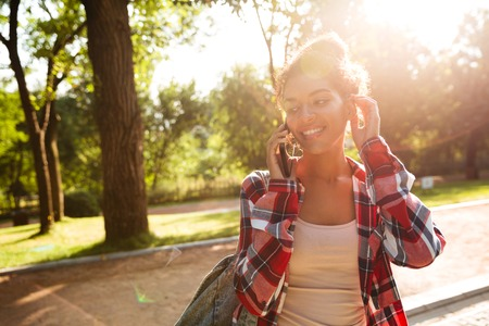Picture of cheerful young african woman walking outdoors in park. Looking aside talking by phone.