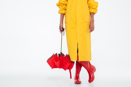 Cropped image of african woman in raincoat with umbrella over white background