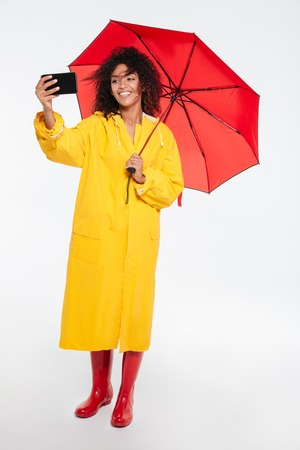 Full length image of happy african woman in raincoat hiding under umbrella and making selfie on her smartphone over white background