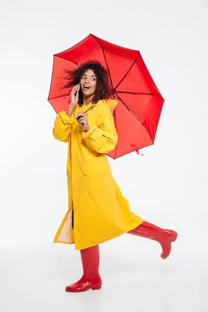 Full length image of surprised happy african woman in raincoat hiding under umbrella and walking in studio while talking by smartphone and looking back over white background
