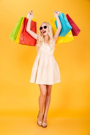 Beeld van gelukkige jonge blondevrouw status geïsoleerd over gele muurachtergrond. Zoek opzij met boodschappentassen.